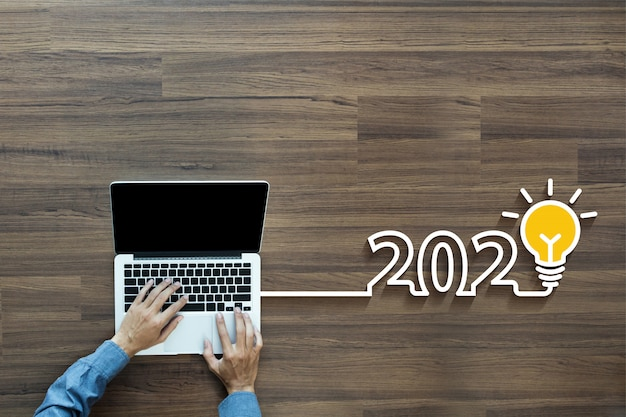 Creatief gloeilampenidee 2020 met zakenman die aan laptop werkt