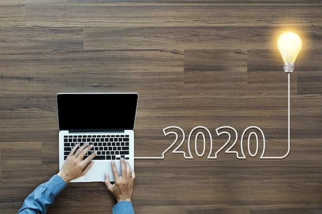 Creatief gloeilampenidee 2020 nieuw jaar, met zakenman die aan laptop werken