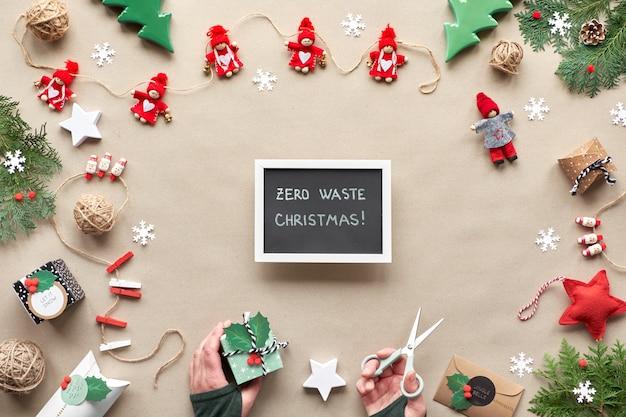 Creatief handgemaakt decor, kerstversiering zonder afval voor het nieuwe jaar. plat lag, bovenaanzicht op ambachtelijk papier. textiel snuisterijen, cadeau in de hand. eco-vriendelijke xmas party concept.