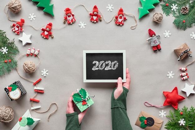 Creatief handgemaakt decor, kerstversiering zonder afval voor het nieuwe jaar. plat lag, bovenaanzicht op ambachtelijk papier. textiel snuisterijen, geschenkdoos in de hand. eco-vriendelijke groene xmas party.