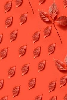 Creatief handgemaakt herfstpatroon van rode druivenbladeren in verschillende vorm en grootte op een koraalachtergrond. plat leggen.