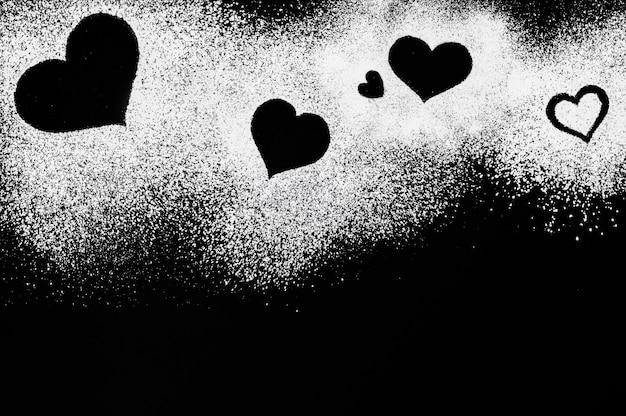 Creatief hart vorm frame gemaakt van wit poeder, geïsoleerde harten op zwarte achtergrond, suiker harten