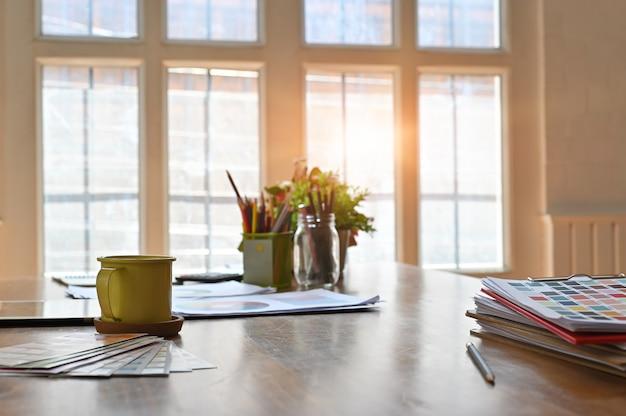 Creatief houten bureau met kleurendocument grafiek en koffiemok.