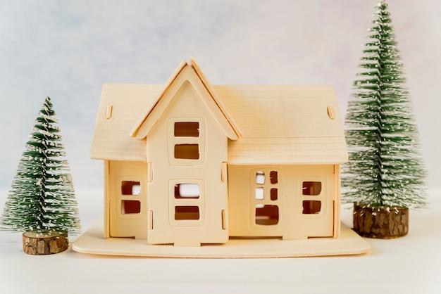 Creatief huis met groene kerstmisbomen op geweven achtergrond