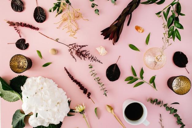 Creatief ingericht en gearrangeerd plat lag concept met hortensia, schelpen, koffie, gouden lepel, takken op roze