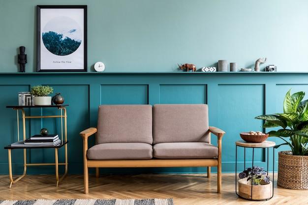 Creatief interieur van gezellige woonkamer met posterframe stijlvolle bank planten design meubels decoratie en elegante accessoires groene muren parketvloer home staging