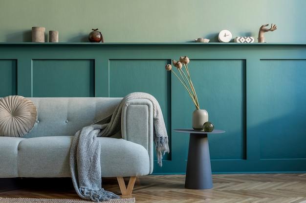 Creatief interieur van woonkamer in gezellig appartement met stijlvolle bank, planten, designmeubels, decoratie en elegante accessoires. groene muren, parketvloer. thuis enscenering. .