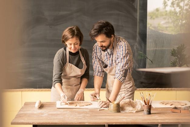 Creatief jong stel in schorten die nieuw ontwerp van kleipunten of aardewerk bespreken terwijl zij over privécollectie werken