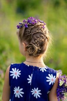 Creatief kapsel van een klein schattig meisje met blond haar op een bloeiende lupine veld. jeugd concept. kinderen en natuur.