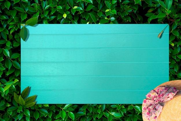 Creatief karakter lay-out gemaakt van tropische bladeren en bloemen met blauwe houtnerf plat lag.