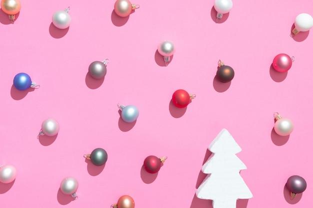 Creatief kerstballen decoratie patroon met kerstboom en roze achtergrond. minimaal plat leggen concept.