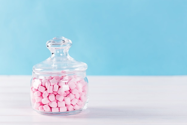 Creatief minimaal stilleven op pastelblauw gekleurde achtergrond. glazen schaal met schattige roze marshmallows.