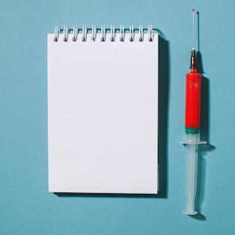 Creatief minimalistisch concept met een rode spuit op een blauwe achtergrond met ruimte voor tekst. vaccin en medicijnen