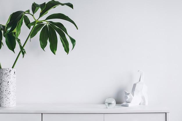 Creatief minimalistisch woonkamerinterieur met kopieerruimte wit modern commodeblad in vaas en sculptuur van witte muren