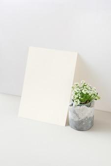 Creatief modern van natuurlijke verse kamerplant in bloei en verticaal vel papier tegen lichtgrijze achtergrond, kopieerruimte. natuurlijk eco-concept.