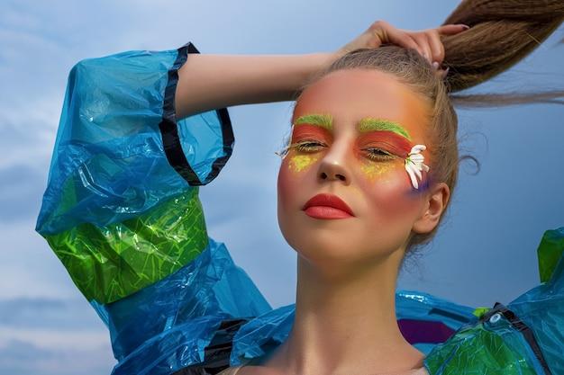 Creatief modieus schoonheidsportret van een mooie jonge vrouw met lang haar in een blauwe regenjas tegen de hemel. professionele make-up. detailopname. lichaamskunst