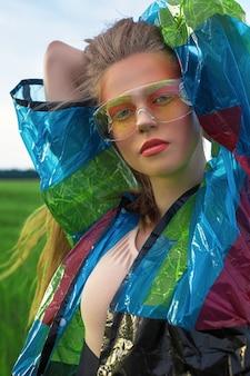 Creatief modieus schoonheidsportret van een mooie jonge vrouw met lang haar in een blauwe regenjas