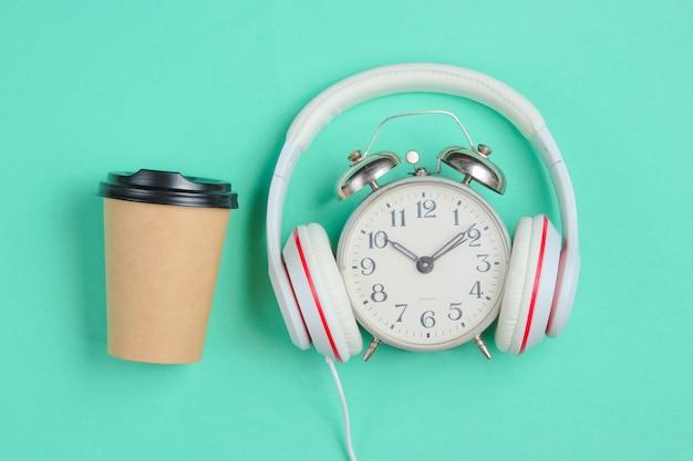 Creatief muziekconcept. retro wekker met klassieke hoofdtelefoons en koffiekopje op blauwe achtergrond.