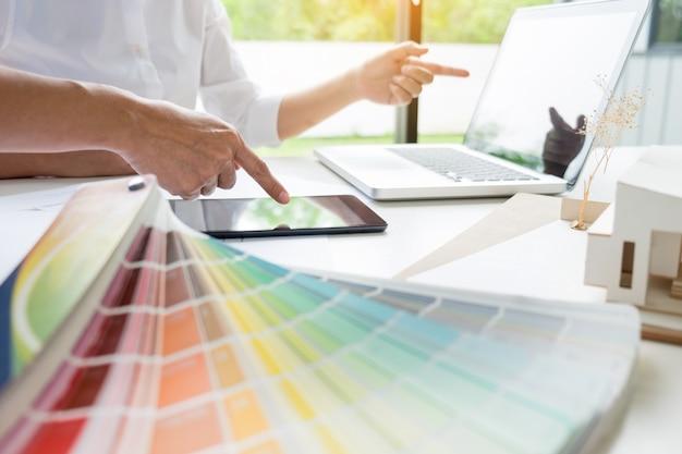 Creatief of binnenlands ontwerpersgroepswerk met pantonemonster en de bouw van plannen op bureau, architecten die kleurensteekproeven voor ontwerpproject kiezen