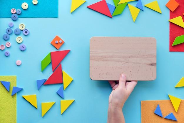Creatief ontwerp voor autisme werelddag met tangram puzzel driehoeken, pictogram en hand met bord
