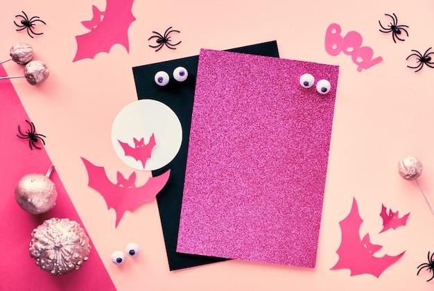 Creatief papier ambachtelijke halloween plat lag in roze, magenta en zwart. bovenaanzicht met cipy-spatie op stapel kaarten, vleermuizen, chocoladeogen, pompoenen en tekst