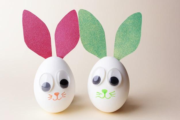 Creatief pasen-concept - eieren in de vorm van konijntjes met papieren oren, decoratieve ogen en geschilderde snuiten. lichte achtergrond, handgemaakt. copyspace.