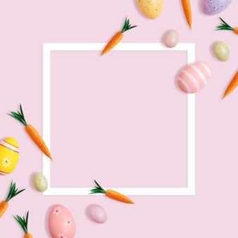 Creatief pasen-patroon van wortelen en kleurrijke eieren op roze achtergrond