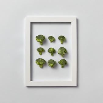 Creatief patroon van natuurlijke vers geplukte biologische broccoli in een frame op een lichtgrijze muur, plaats voor tekst. bovenaanzicht. vegetarisch voedselconcept.