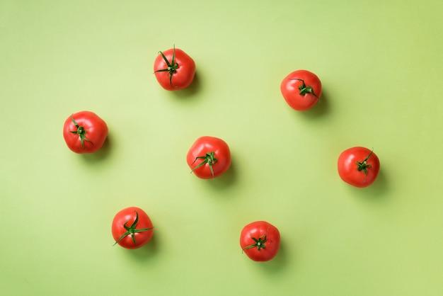 Creatief patroon van rode tomaten. minimaal ontwerp. vegetarisch, veganistisch, biologisch voedsel en alkalisch maaltijdconcept