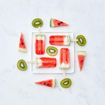 Creatief patroon van verschillende stukjes fruit en bessenkleurijs op een stokje in de vorm