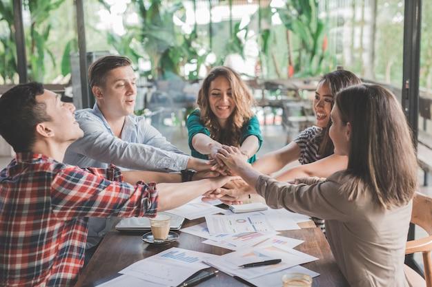Creatief plan zakelijk teamwerk dat eenheid in diversiteit toont door hun handen in elkaar te steken