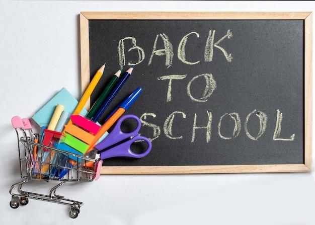 Creatief plat bovenaanzicht terug naar schoolconcept, winkelen voor school. gekleurde schoolbenodigdheden in een winkelwagentje en zwart bord op een witte achtergrond, kopieerruimte, ontwerp