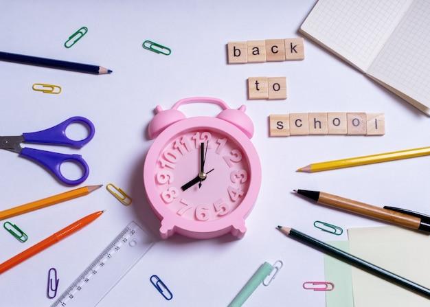 Creatief plat lag bovenaanzicht terug naar schoolconcept, zomertijd, onderwijsconcept. gekleurde schoolbenodigdheden en roze wekker op witte achtergrond, kopieer ruimte, ontwerp