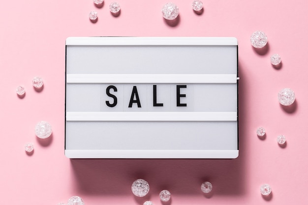 Creatief plat lag bovenaanzicht van verkoop tekst op de lightbox en glanzende decoraties op roze achtergrond. feestelijk verkoop- en promoconcept. zwarte vrijdag