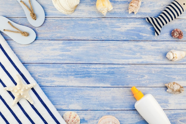 Creatief plat lag concept van zomervakanties. bovenaanzicht van strandlaken zonnebrandcrème fles flip-flops schelpen zeester pastel blauwe houten planken achtergrond met kopie ruimte mockup sjabloontekst