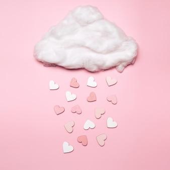 Creatief plat leggen van hartvormobjecten die uit de wolk op pastelruimte vallen. liefde concept