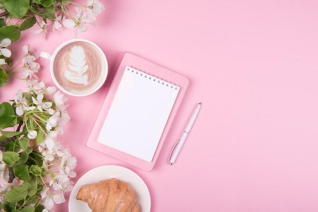 Creatief plat leggen van werkruimtebureau, notitieblok en lentebloesem op roze achtergrond. kopieer ruimte