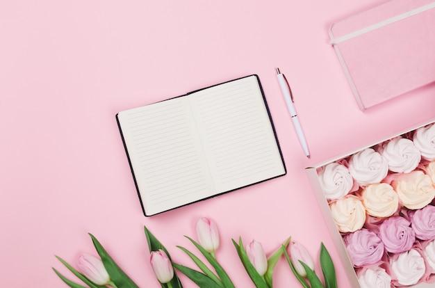 Creatief plat leggen van werkruimtebureau, notitieblok voor verlanglijst en lifestyle-objecten op roze tafel