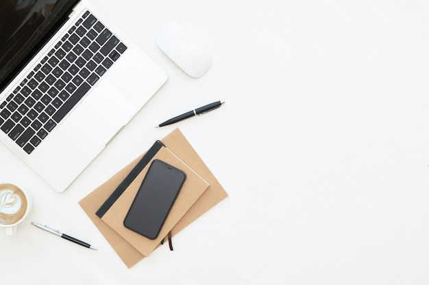 Creatief plat ontwerp van werkruimtebureau met laptop, laptop, blanco notebook, smartphone en briefpapier met kopieerruimteachtergrond