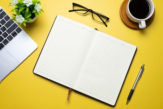 Creatief platliggend bureaublad met notitieboekje de koffiemok wordt op het gele gebied geplaatst. ruimte kopiëren