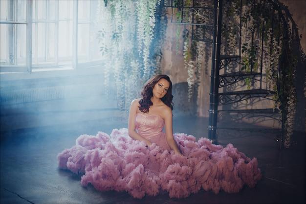 Creatief portret van een mode-vrouw in prachtige lange roze romantische jurk