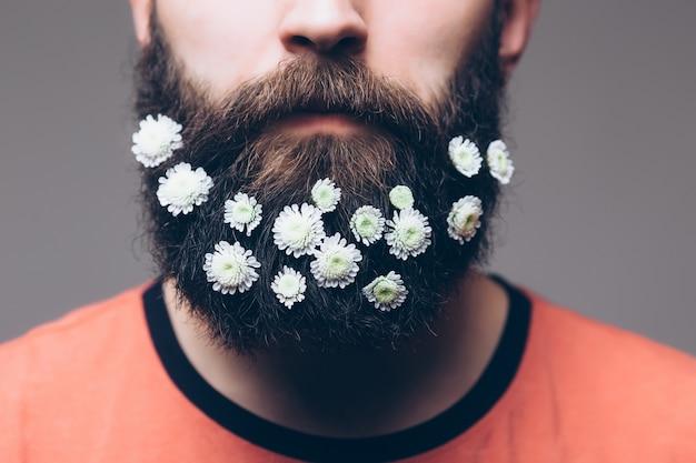 Creatief portret van jonge mooie man met een baard versierd met bloemen.