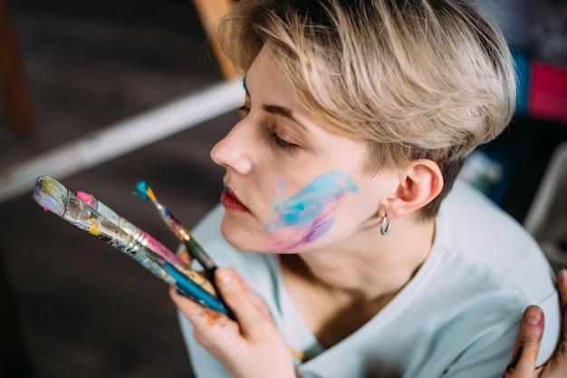 Creatief portret van mooie jonge vrouwenkunstenaar in studio met borstels