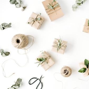 Creatief regelingspatroon van ambachtelijke dozen en groene takken op witte achtergrond.