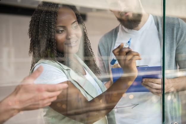 Creatief team die bedrijfsstrategie trekken bij bureauvenster.