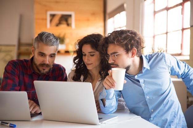 Creatief team kijken naar projectpresentatie op laptop