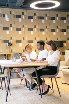 Creatief team samen aan tafel zitten met blauwdrukken en werken aan project