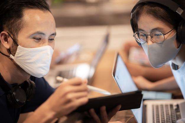 Creatief werkersteam dat gezichtsmasker draagt, dat bij zakelijke co-werkruimte werkt
