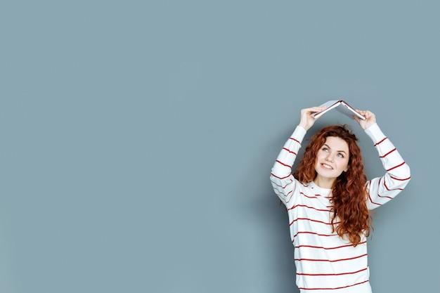 Creatief zijn. positieve vrolijke aardige vrouw die tegen een grijze achtergrond staat en een boek gebruikt terwijl ze het boven haar hoofd houdt