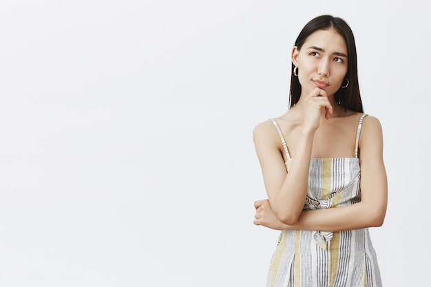 Creatieve aantrekkelijke aziatische vrouwelijke ontwerper van kleding in bijpassende outfit, hand op kin, dromerig op zoek terwijl je ideeën bedenkt of iets plant, nadenkend over grijze muur staat